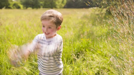 throwing in : Little boy throwing confetti in the air and playing in the park