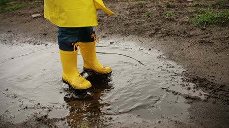 ботинок : Young child jumping in muddy puddle in slow motion