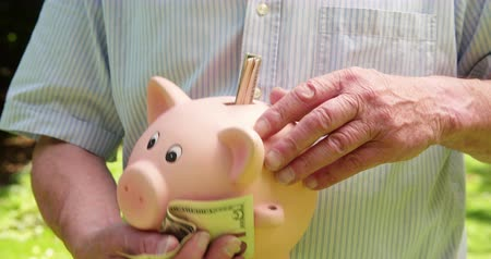 emekli : Man putting money into a piggy bank for saving