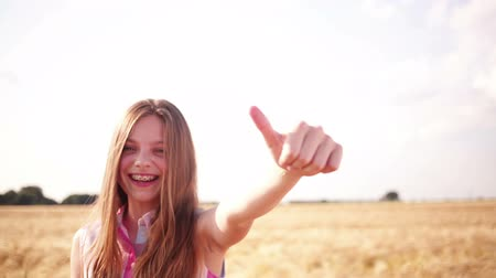 braces smile : Young girl showing thumbs up to camera in wheat field and smiling Stock Footage