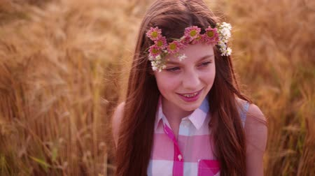 braces : Young girl having a good time walking through wheat fields