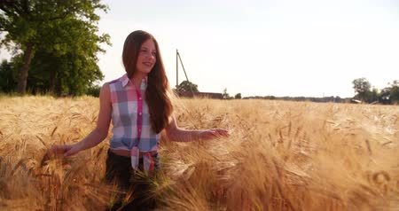 braces : Young girl walking through wheat fields in slow motion