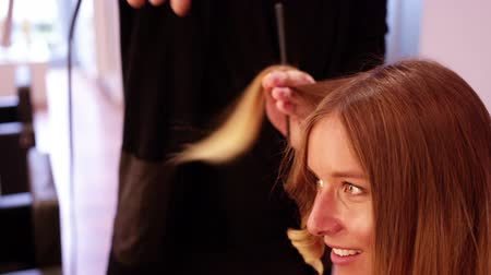 curling hair : Woman having her hair styled in hair salon