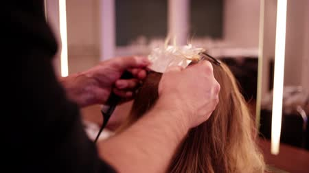 kadeřník : Hairdresser prepares foil highlights in womans hair