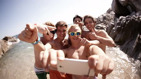 друзья : Group of guy friends taking selfie at the beach