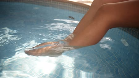 treading : Womans legs in water at poolside