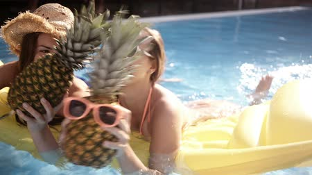 ananas : Girls having a silly time with pineapples in swimming pool