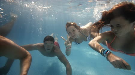 plavání : Friends having fun swimming underwater in swimming pool