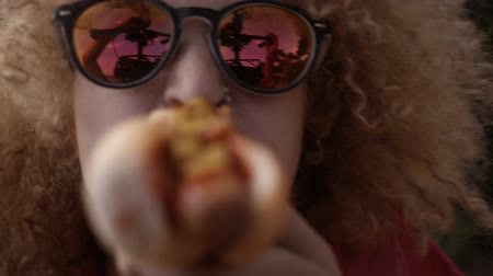 morder : Girl biting into hotdog close to camera Stock Footage