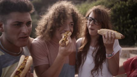 man eating : Friends enjoying biting into hotdogs together