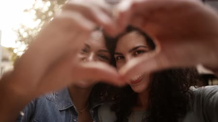 kéz a kézben : Best mixed race girl friends show heart shape to camera with hands