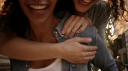 девушка : Laughing best mixed race girl friends piggyback one another in urban area