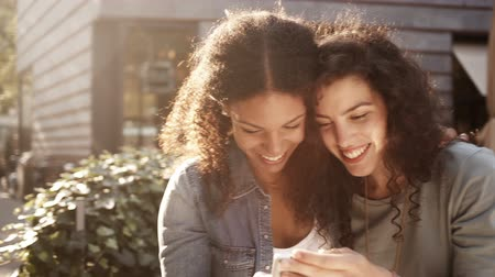 друг : Mixed Race Girl friends look at smart phone together and smile
