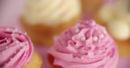 queque : Closeup pan of beautifully decorated pink and white cupcakes Vídeos