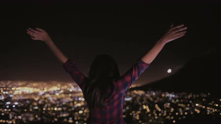 juventude : Young woman happily raising up her arms with all the citys lights spread out beyond