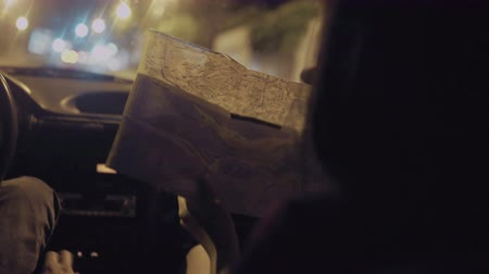 gösterge paneli : Woman reading map in driving car in night time city