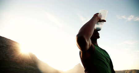 diadal : Athlete drinking from a water bottle in slow motion outdoors during an early morning run Stock mozgókép