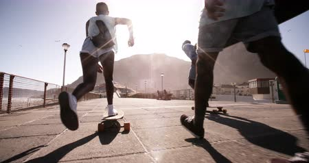 longboarder : Cool group of African American teenagers casually longboarding together on a walkway down at the beach in Slow Motion