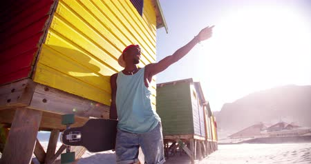 longboarder : Cool African American guy posing with his longboard at the beach Stock Footage