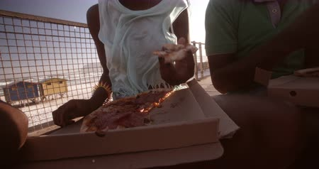 longboarder : Close up of african american girl eating a slice of pizza