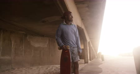 longboarder : Afro american teenage guy standing under overpass with longboard