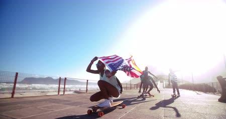 longboarder : Teenage African American skater flying an American flag past the camera in Slow Motion
