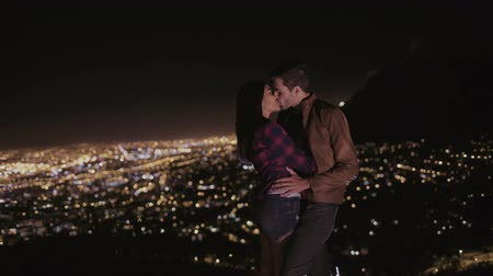 смешанной расы человек : Young couple kissing with the city lights spread out in the background