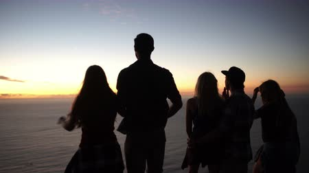 kaland : Group of teens on a mountain looking out at the ocean after a peaceful sunset Stock mozgókép