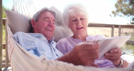 emekli : Loving senior couple using their digital tablet in a hammock together in their retirement in Slow Motion Stok Video
