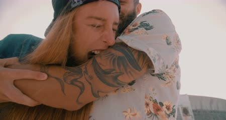 morder : Playful hipster girl pretending to take big bite out of her boyfriends tattooed arm while hanging out at the beach Stock Footage