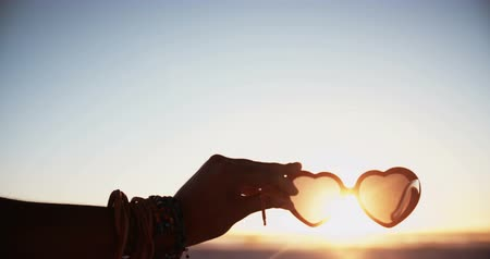 szív alakú : Cropped shot of a womans hand holding a pair of heartshaped sunglasses at sunset on a beach