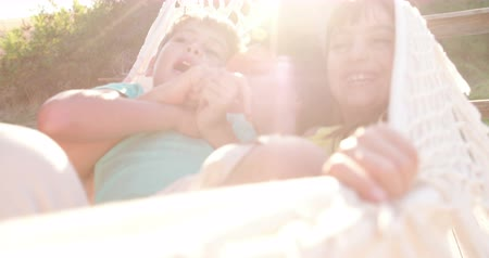 Mom and children sharing a hammock laughing together on a wooden porch with sun flare in Slow Motion Стоковые видеозаписи