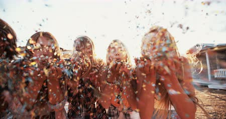 Row of teens celebrating by blowing colorful confetti on a summer evening outside Panning in Slow Motion Стоковые видеозаписи