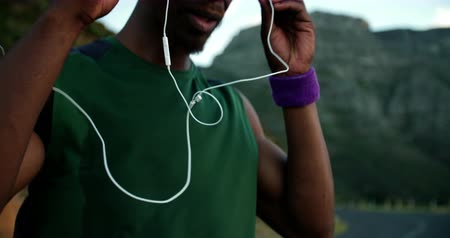 африканского происхождения : African American runner putting his earphones in before his starts his fitness training in slow motion Стоковые видеозаписи