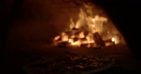 italian speciality : Freshly made pizza being placed carefully inside a traditional wood fire oven in Slow Motion