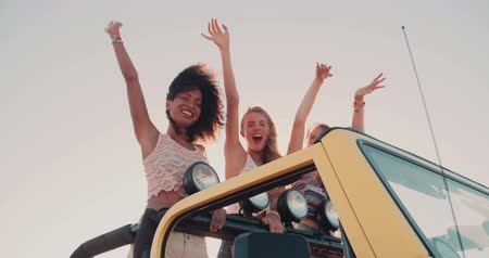 viagem por estrada : Afro girl and friends dancing in the back of their vehicle on a road trip to the beach in Slow Motion