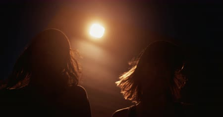 városi : three teenage grunge girl friends walking at night on an urban road with lens flare from street light Panning in Slow Motion