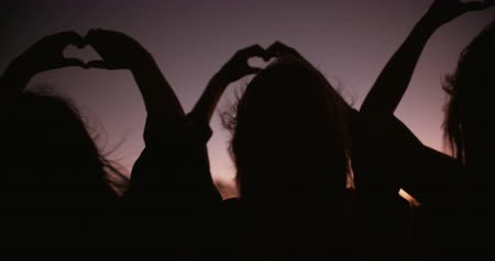 person's hand : Silhouette of teens using their hands to make heart shapes against dusk sky Stock Footage