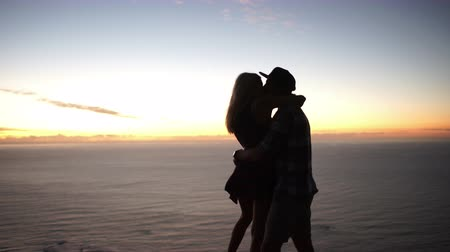 outside : Twilight silhouette of a romantic young couple hugging each other on a mountain with the sea in the background Stock Footage