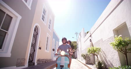 vacation : Couple sitting on their scooter in a quiet street having fun on a road trip vacation in Slow Motion