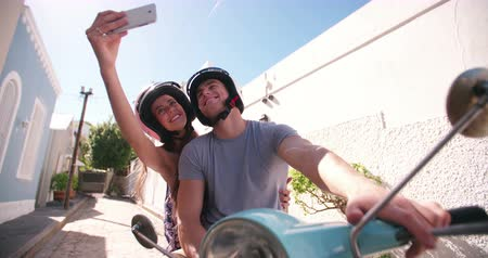 skútr : Loving couple sitting on a scooter with the girl taking a selfie of them together in Slow Motion