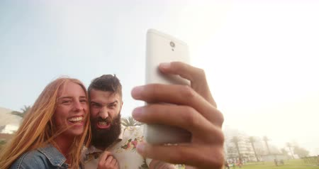 hipster : Hipster guy pulling funny face while taking a selfie with his laughing girlfriend outdoors