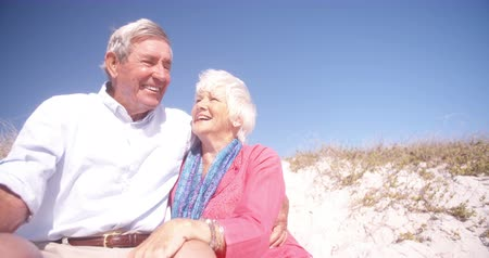 életerő : Laughing retired senior couple sitting happily on a sand dune at the beach together in Slow Motion