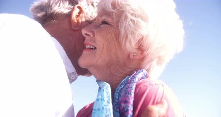 életerő : Senior couple with the loving elderly man kissing his wife affectionately at the beach in Slow Motion Stock mozgókép