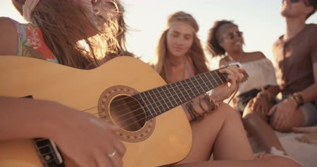večer : Girl playing her guitar for her friends at a beachparty on a summer evening in Slow Motion