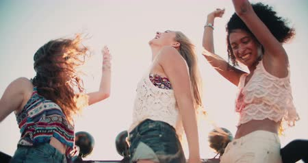 uliczki : Mixed racial group of girl friends dancing happily while standing in their vehicle at the beach on a summer vacation road trip Wideo