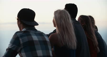 outside view : Rear view of a group of teens sitting on a mountain together watching a sunset in Slow Motion Stock Footage