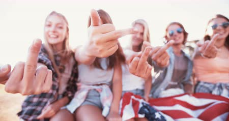 жест : Group of rebellious teenagers holding an American flag while showing their middle fingers  Panning in Slow Motion