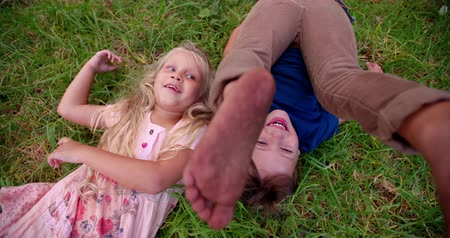 yuvarlanma : Boy rolling in grass with girl lying next to him in slow motion both having fun Stok Video