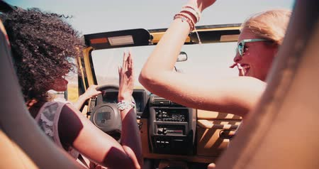viagem por estrada : Two teen girls one afro and one blonde high fiving in vehicle on a road trip to the beach for summer vacation in Slow Motion Stock Footage
